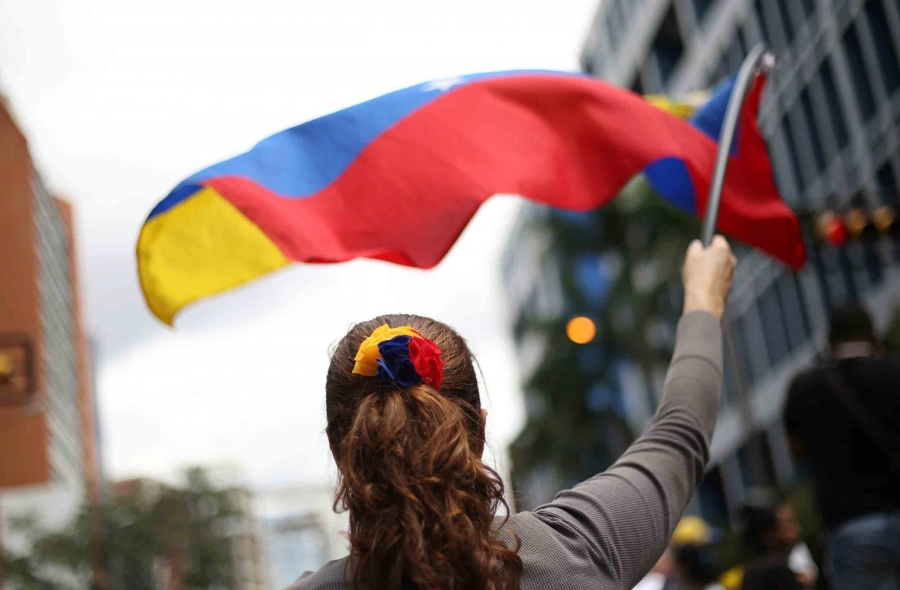 A woman stands with her back to the camera and waves a Venezuelan flag in front of her