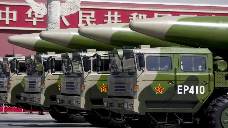Green-colored military vehicles carry DF-26 ballistic missiles.