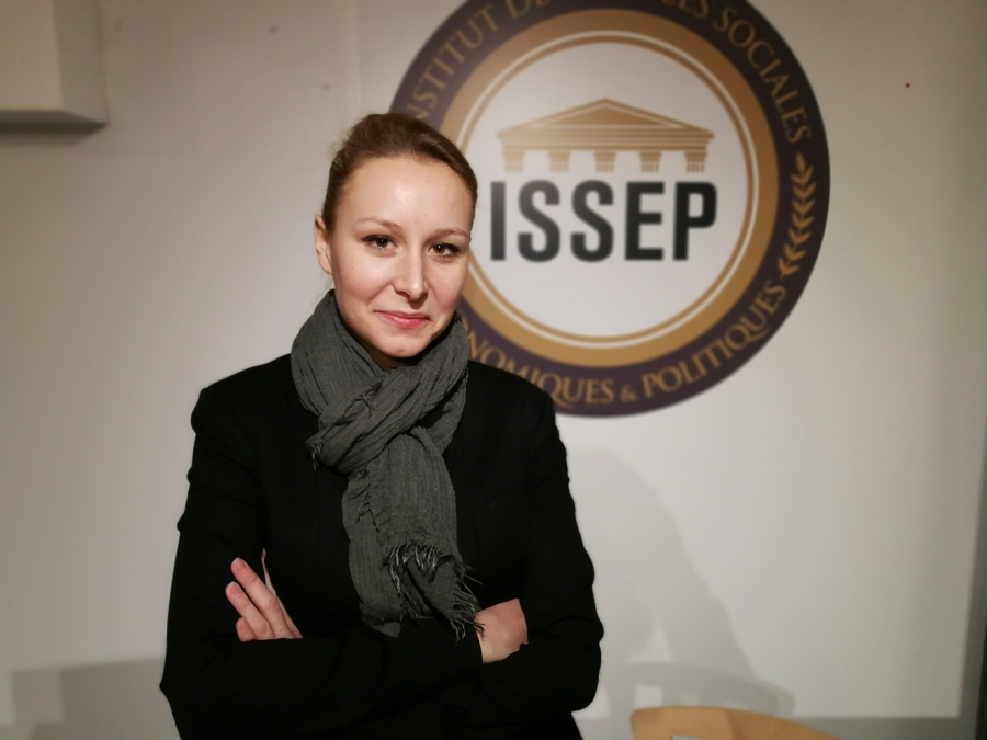 Marion Maréchal stands with her arms crossed in front of a ISSEP sign