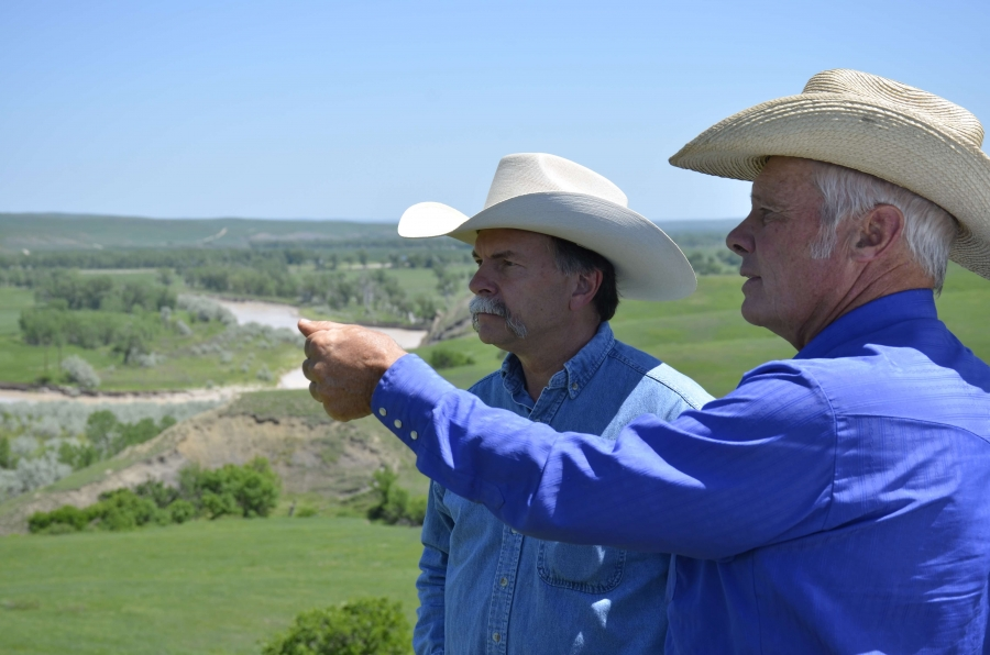 two men wearing cowboy hats stand on a ranch and point