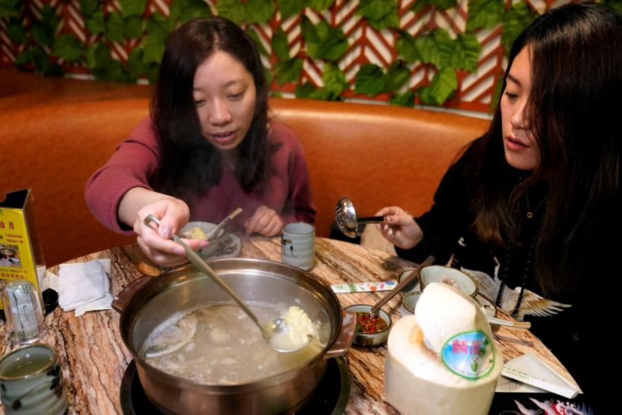 two women eating durian hot pot
