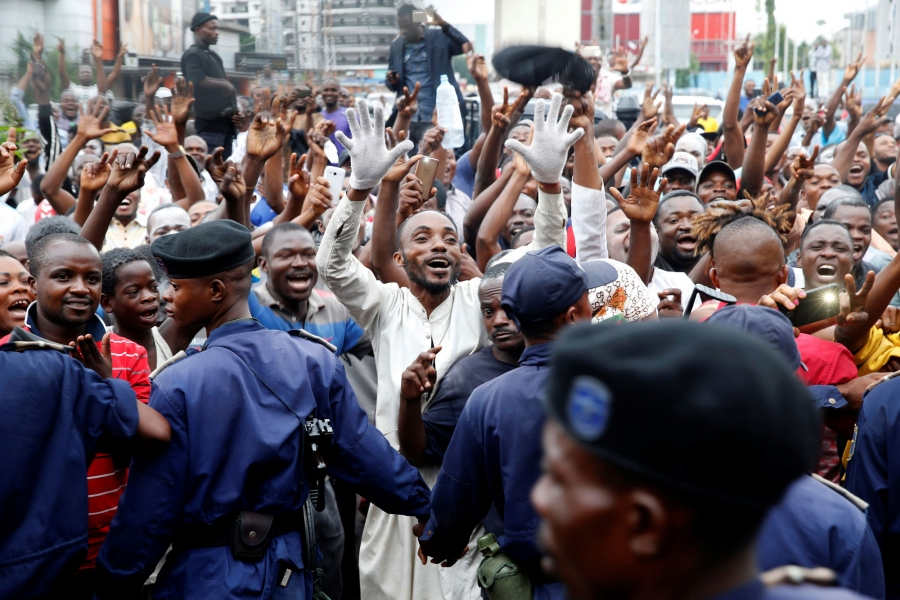 Supporters of Felix Tshisekedi are shown with their hands in the air celebrating in the streets of Kinshasa, Democratic Republic of Congo.