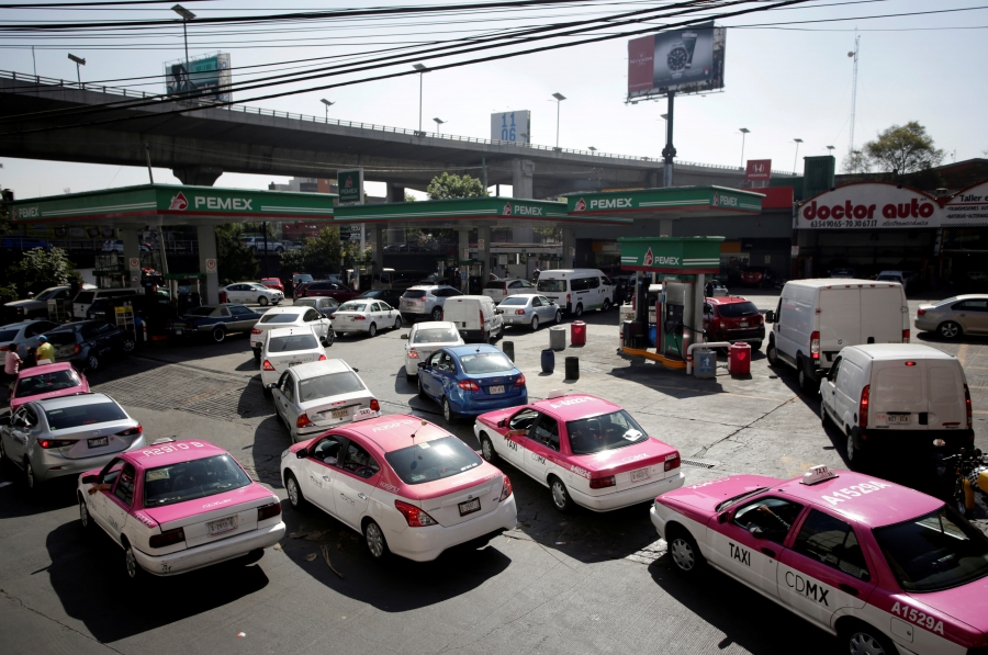 dozens and dozens of taxis line up around a fuel station