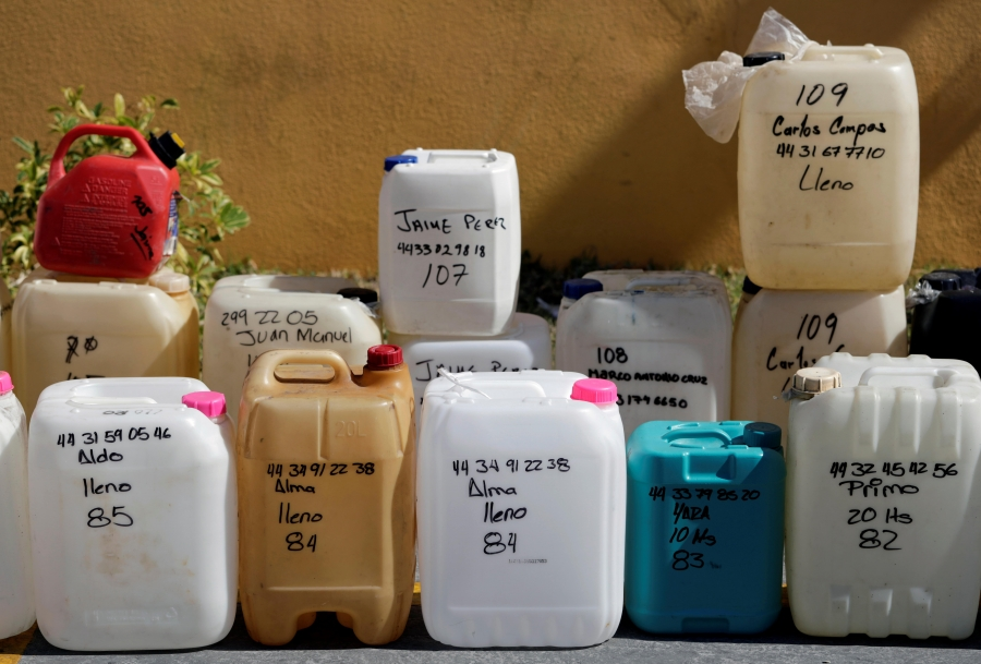 Empty containers are lined up at a gas station,