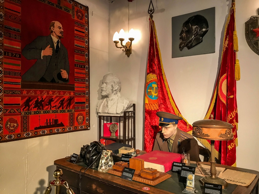 The museum's recreation of a KGB office featuring a desktop calendar and a copy of the Communist newspaper, Pravda, with flags shown behind a uniformed mannequin.