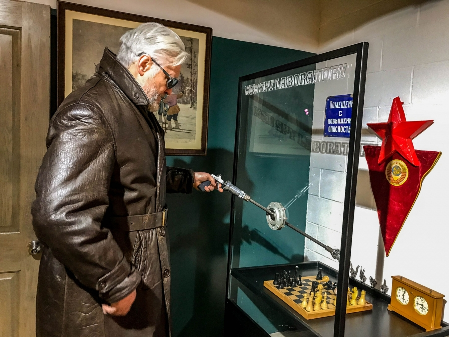Julius Urbaitis is shown demonstrating a device (reminiscent of arcade claw toy-grabber games) that KGB officers used to mix poison without contaminating themselves.