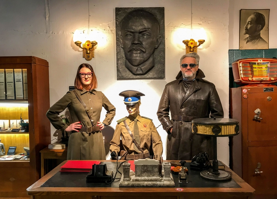 Father-daughter curators Julius Urbaitis and Agne Urbaityte pose behind a desk of a mannequin KGB duty officer wearing vintage military attire.