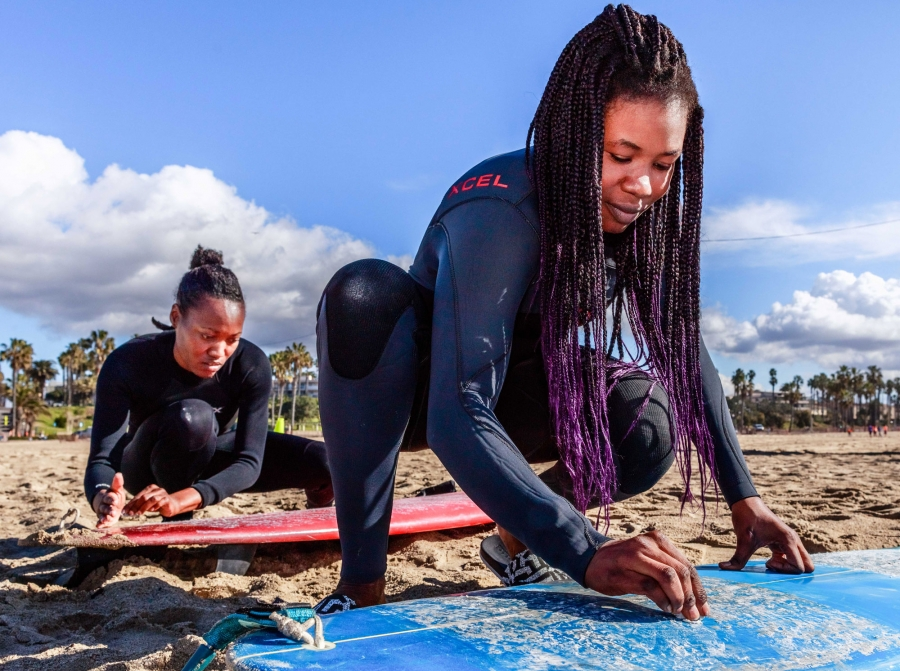 Two women wax their surfboards