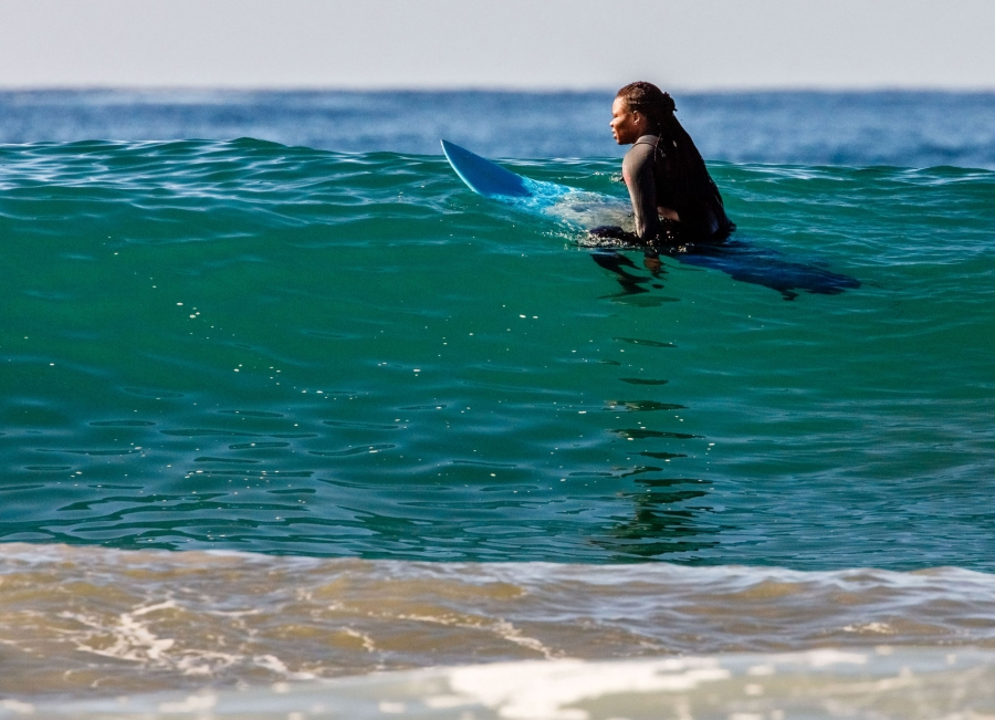 A woman sits on her board waiting for a wave
