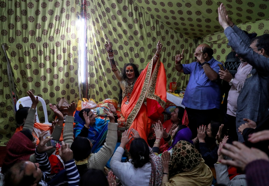 A transgender Indian woman in front of a crowd with hands raised