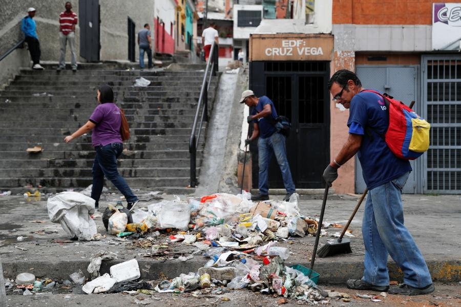 a man sweeps piles of litter