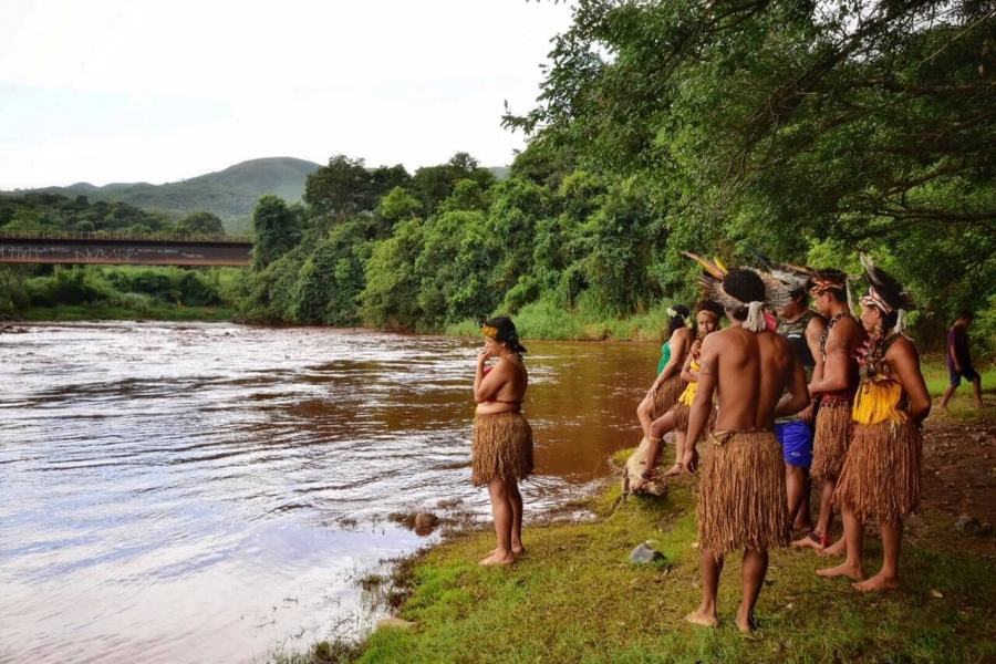 Indigenous people stand on the banks of a flooded river