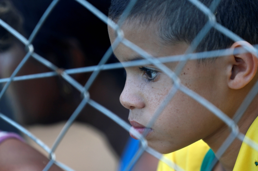a closeup of a young boys face peering through a fence
