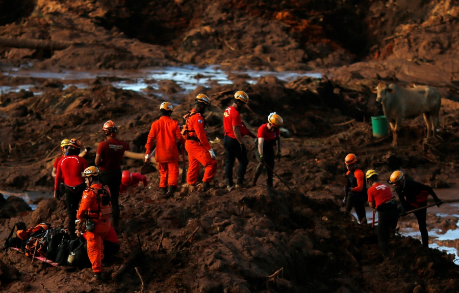 Members of a rescue team search for victims in a sea of red mud