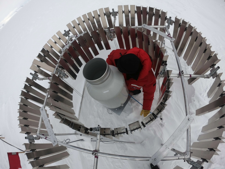 Metallic fins encircle a man in a red coat