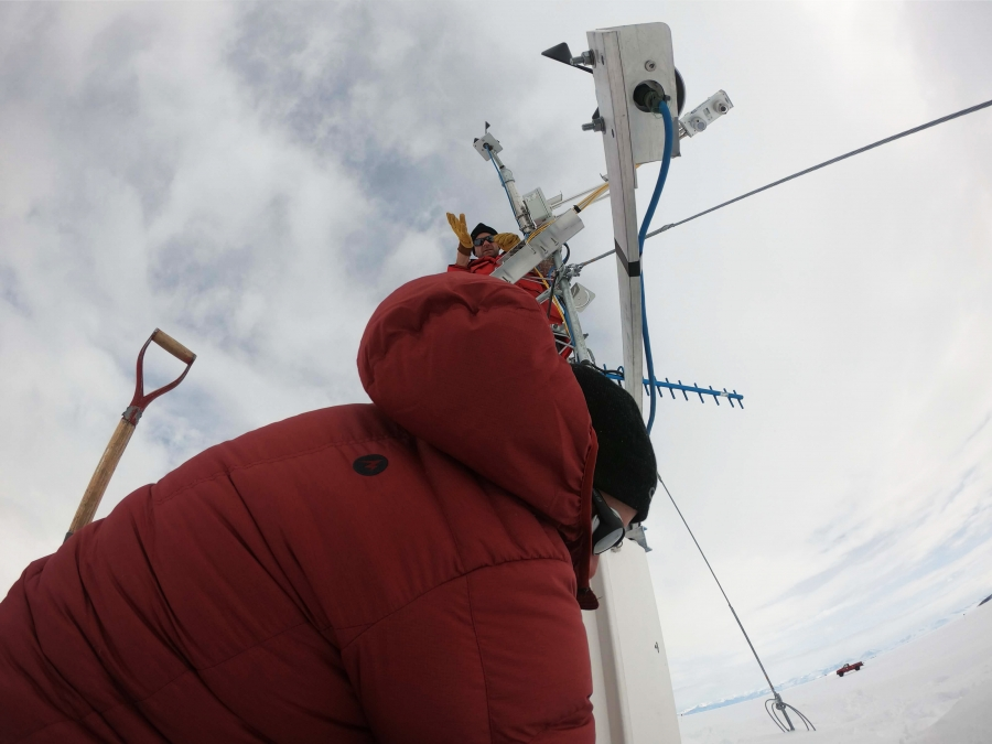 a man in a red coat stands at the bottom of a tall white pole