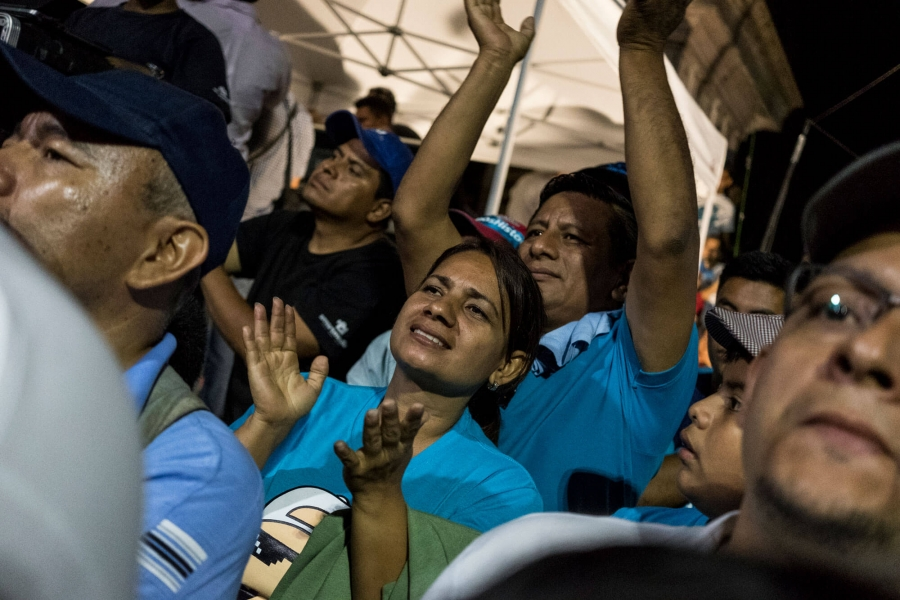 Young Salvadoran woman in blue shirt at a rally.