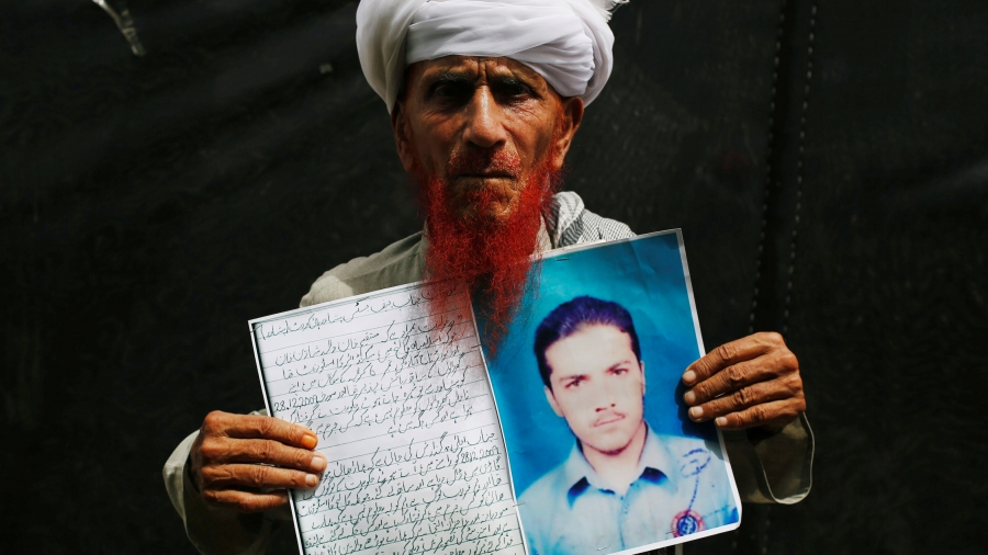 A man in white turban holds photo of his missing son.