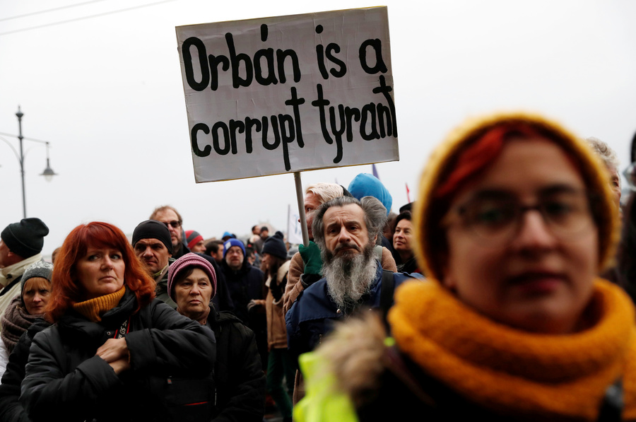 Protester man with beard holds sign against Orban.