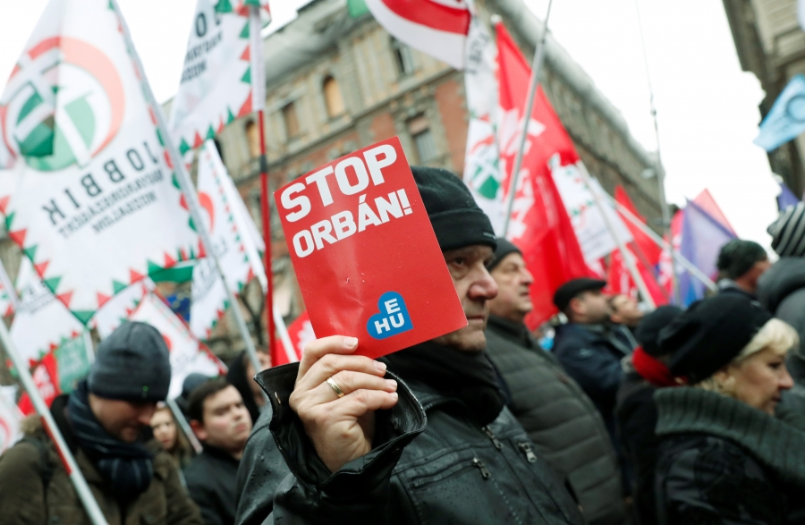 """Protesters hold sign that says """"Stop Orban."""""""
