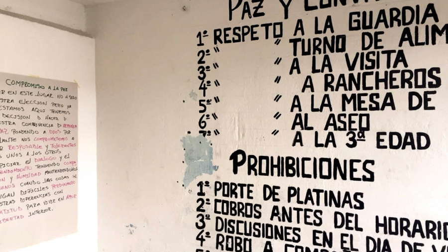 Writing in Spanish on a white wall.
