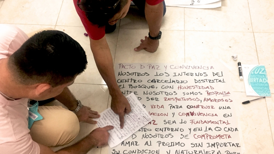 Two men sit on the floor and lean over a piece of paper with writing on it.