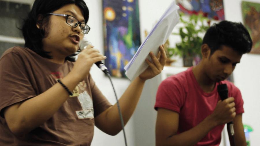Two young men speak into microphones.
