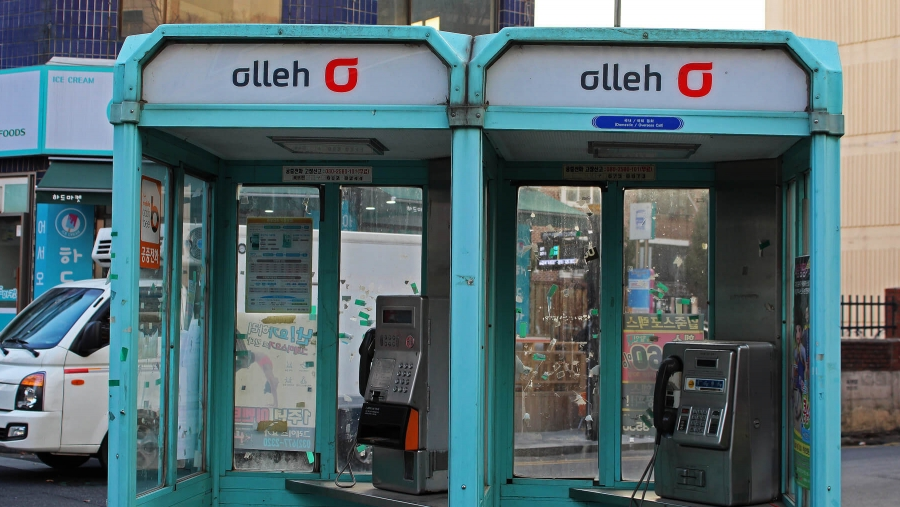 Two old turquoise phone booths side by side in South Korea.