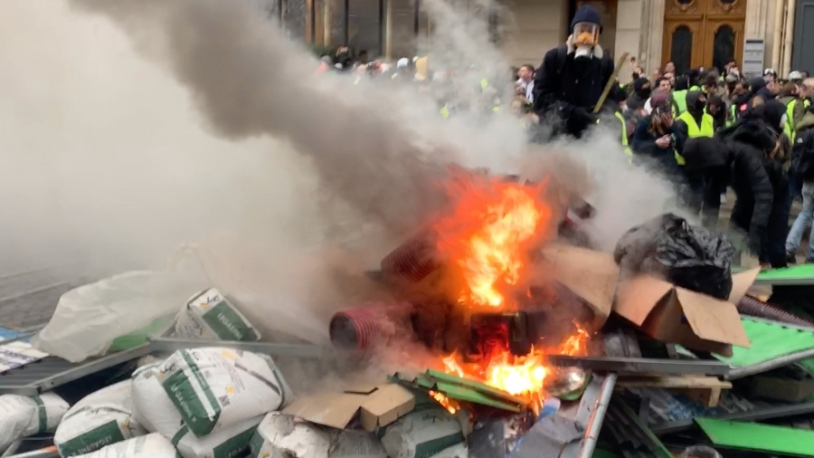 Protesters set fire to a pile of boxes.