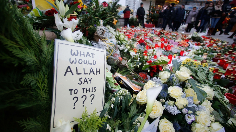 "A card reads ""what would Allah say to this?"" next to bouquets of flowers."