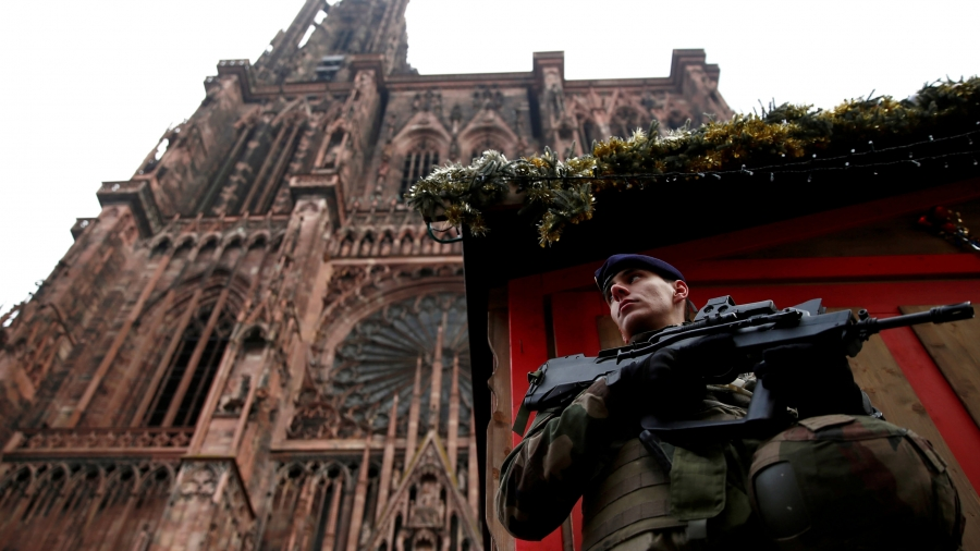 A soldier with a gun stands guard in front of a looming Cathedral.