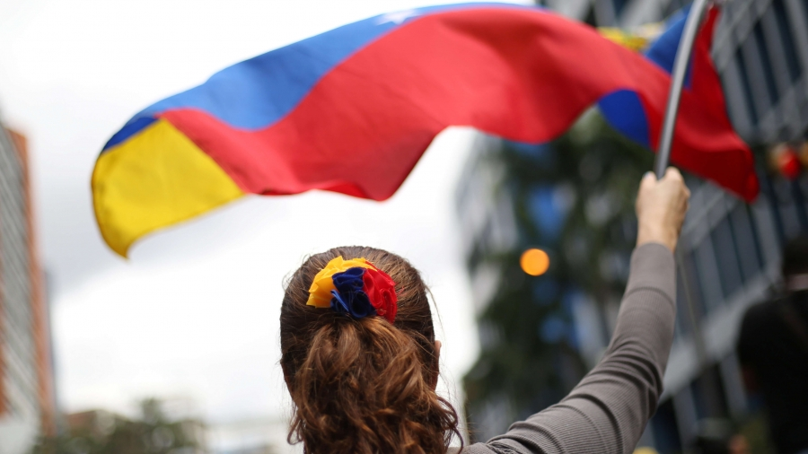 A woman waves red, blue and yellow flag.