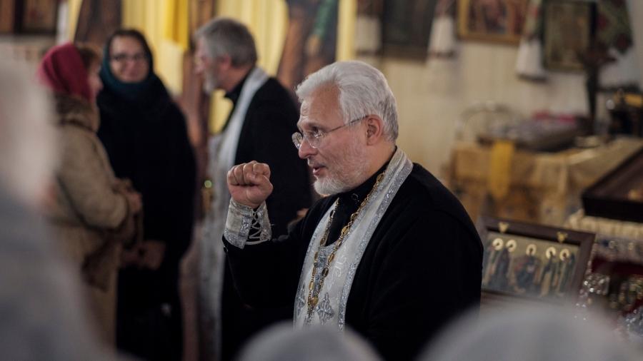 A priest makes a fist.