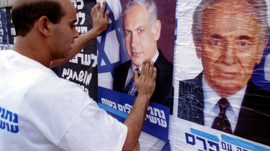 A man pastes a poster with the face of Netanayhu over the poster of Israel's then-prime minister.