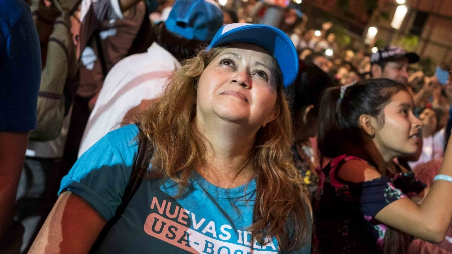 A woman wearing blue looks up at a rally in San Salvador.