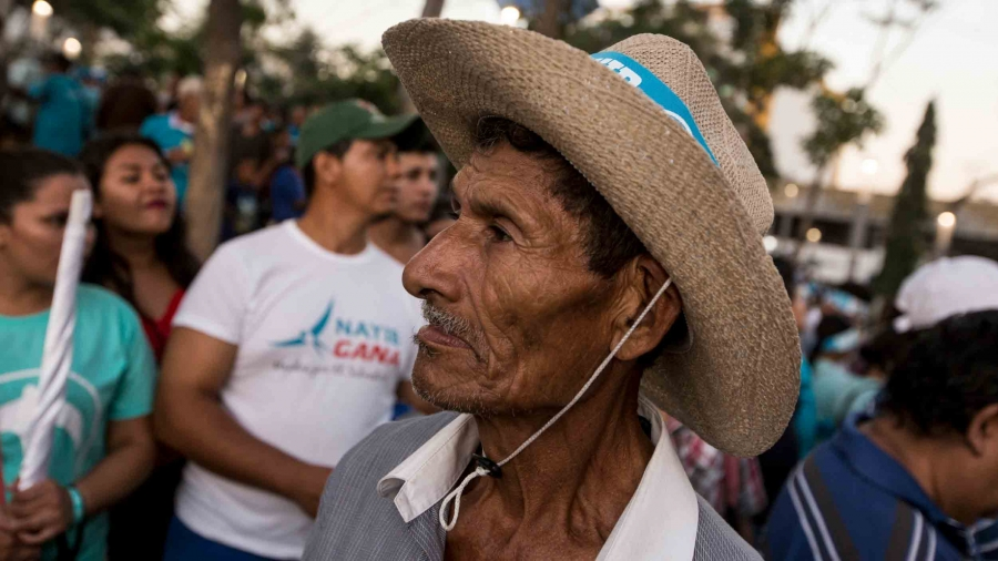 An older man at a political rally in San Salvador.