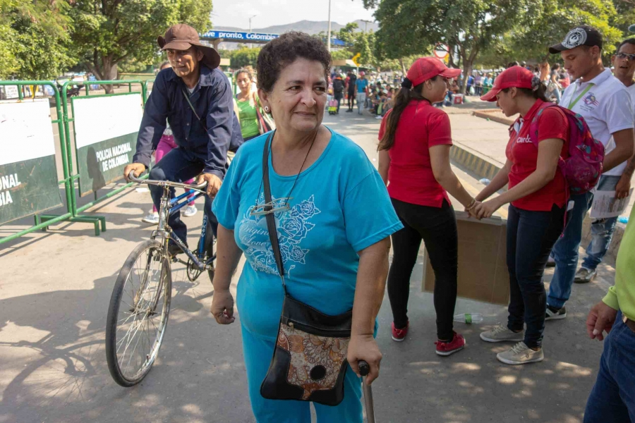 A woman in her 60s walks with a cane and wears a light blue shirt and slacks with glasses around her neck.