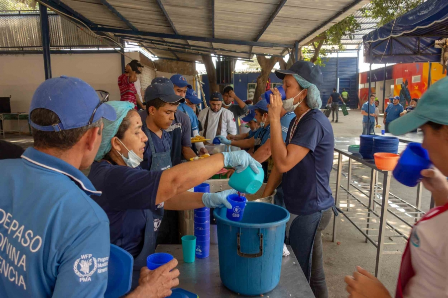 Many people wearing blue shirts stand over pots of food.