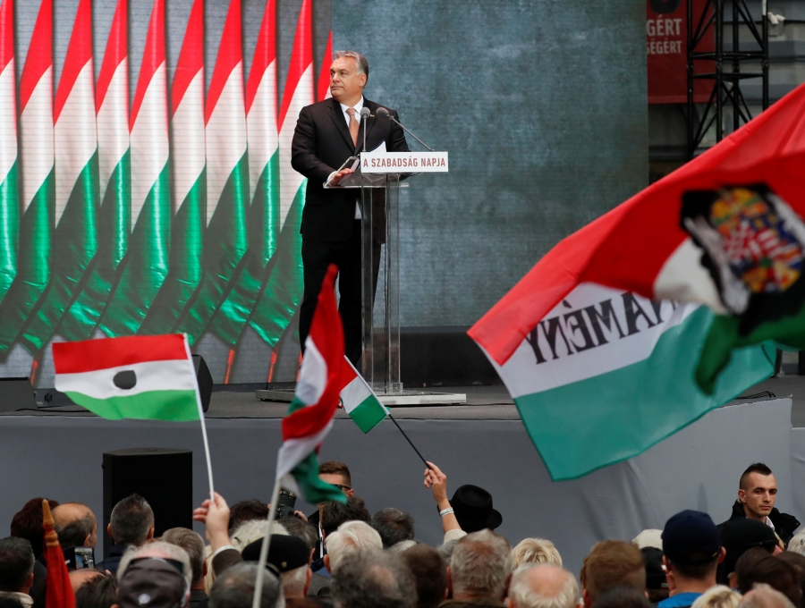 Hungarian Prime Minister Viktor Orbán stands at a podium on a stage above a crowd of people, many of whom are holding Hungarian flags.