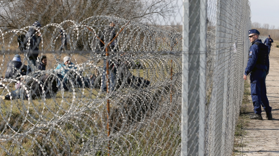 A Hungarian police officer, right, watches migrants through a chain link fence and a fence made of razor wire.