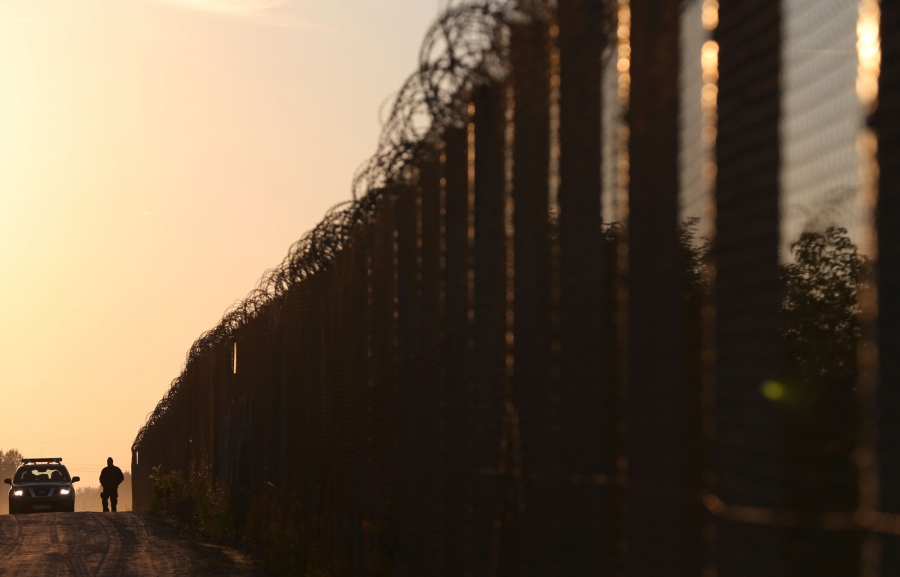 A police officer and a tall fence topped with razor wire is silhouetted against an orange sky.