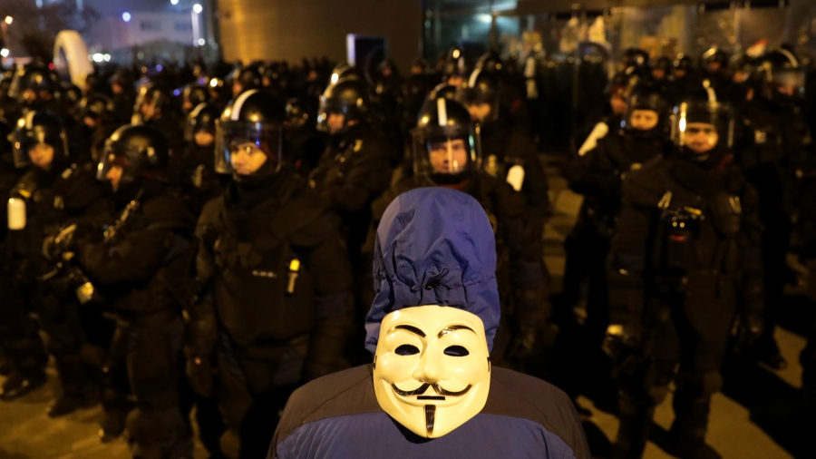 A man stands with his back to the camera. On the back of his head is a Guy Fawkes mask. In front of him are dozens of police wearing riot gear.