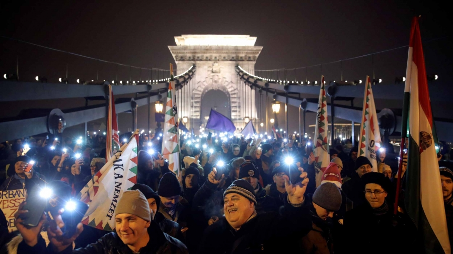 Protestors are crowded onto a bridge that is lit up behind them as they hold their cell phones in the air with the camera flashes turned on.