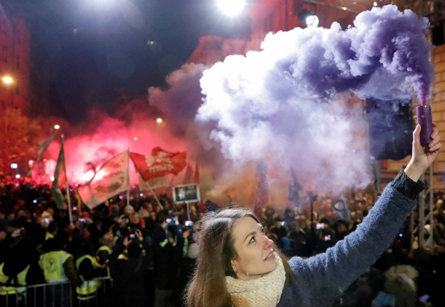 A woman olds a purple flare up the air. Behind her, police clash with protestors in the street.