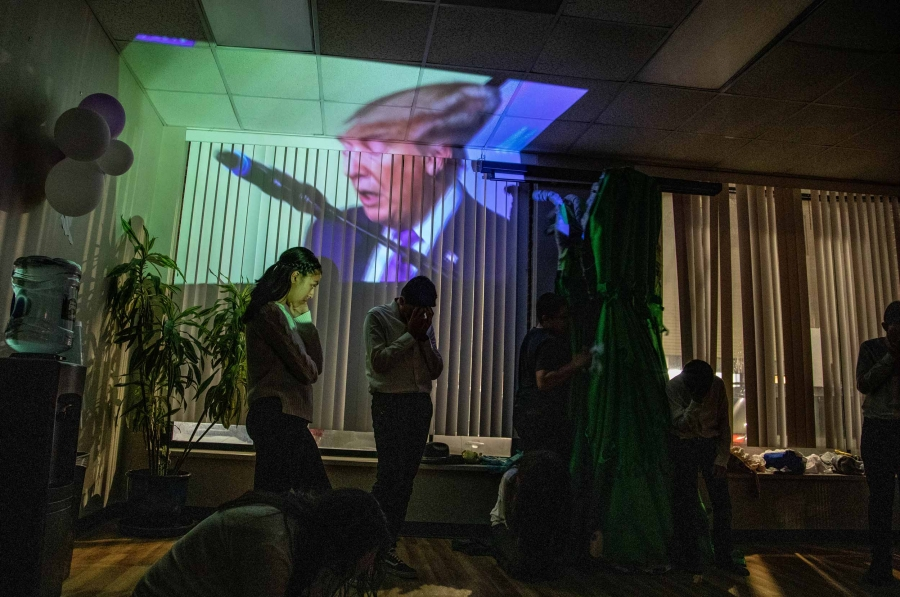 Images of Donald Trump is projected on the wall of a building. Silhouettes of the actors are in front of the image.