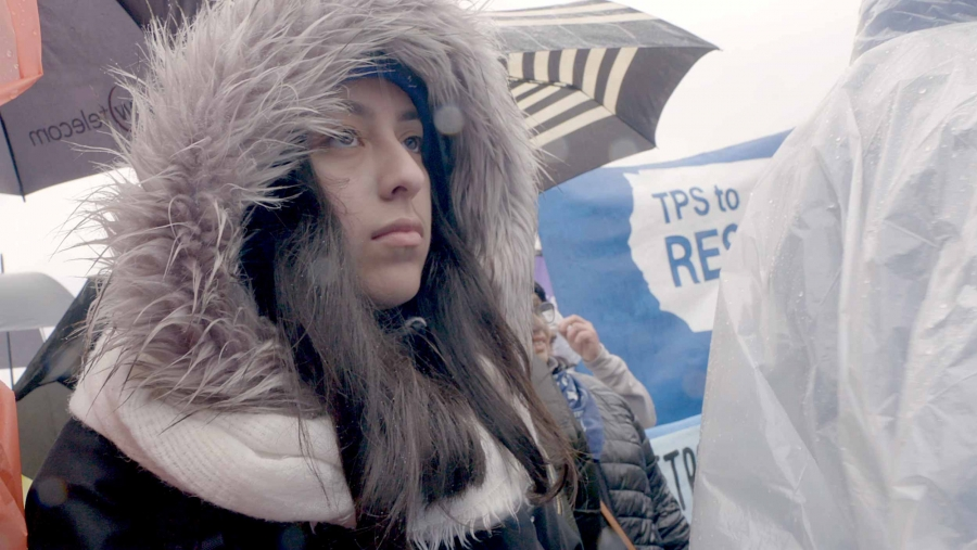 A close-up photo of a young woman wearing a furry hood at a TPS protest with blue signs in the background.