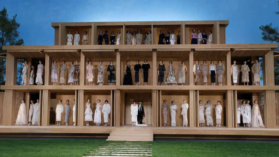 Models are standing on three levels of a wooden house as part of a spring fashion show.