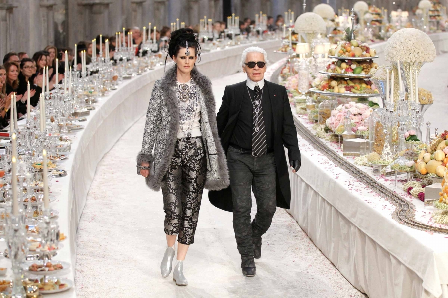 British model Stella Tennant walks with designer Karl Lagerfeld through a runway where people are seated as if for a giant banquet, with candles, crystal and piles of colorful food.