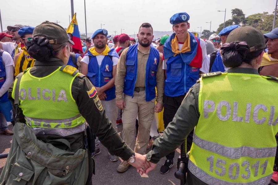 Venezuela volunteers stand in front of Venezuelan police at the border.