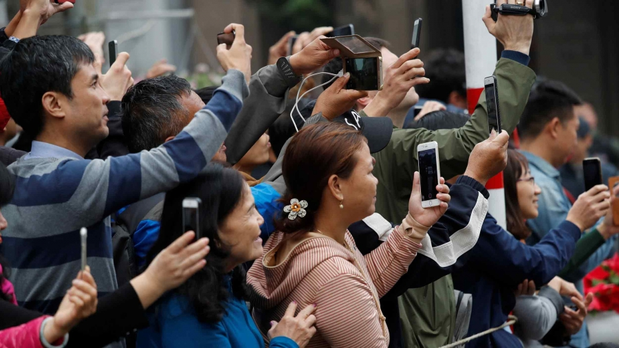 A crowd of people hold phones and cameras to take pictures as the motorcade carrying Kim Jong-un passes by
